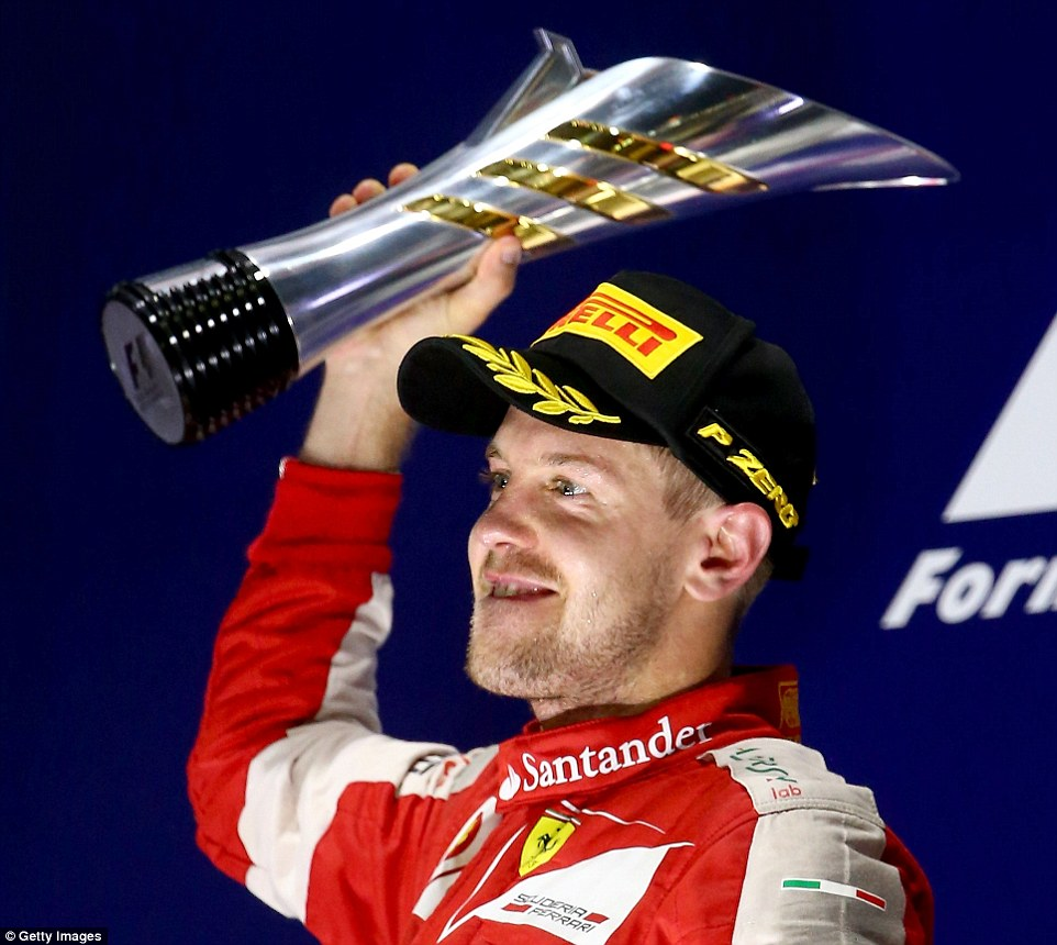 The crowds cheer Vettel as he lifts the trophy on the podium in Singapore after dominating the race throughout