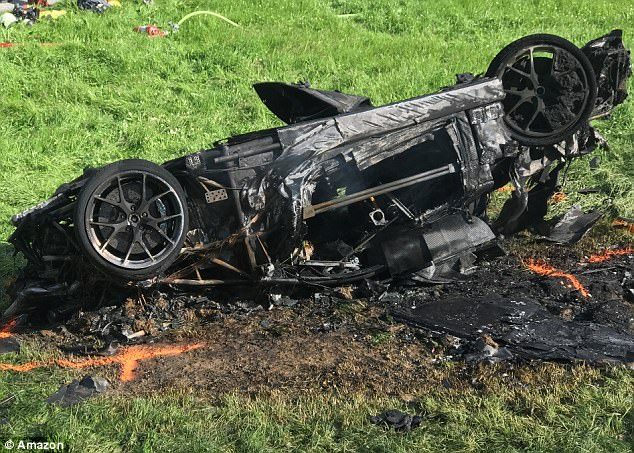 Shocking: Amazon later released this image showing the burnt-out wreckage of the car laying upside down on a hill