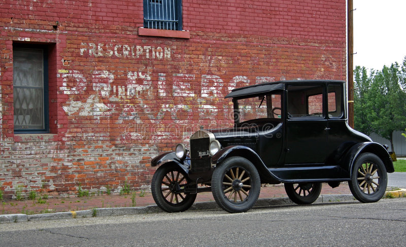 1926 Model T & Brick Building. 1926 Model T Ford parked next to an old drug store stock photo