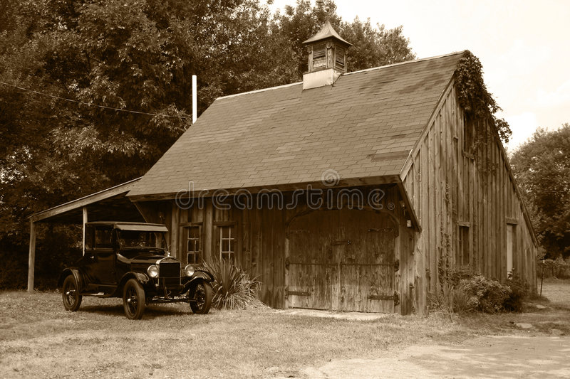 1927 Model T Ford & Old Barn. 1927 Model T Ford coupe parked in front of an old barn, sepia tone stock image