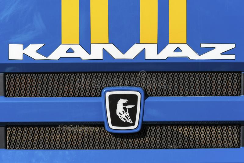 Badge and logotype of Russian truck KAMAZ on front car cabin. KAMCHATKA, RUSSIA - OCT 2, 2018: Badge and logotype of truck KAMAZ and sticker orange-blue stripes stock image