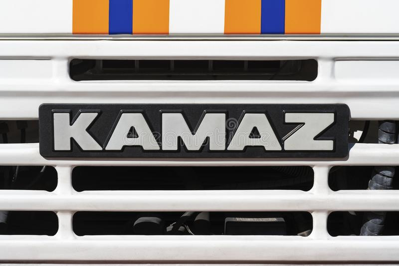 Badge of Russian truck KAMAZ on front car cabin. KAMCHATKA PENINSULA, RUSSIA - OCT 2, 2018: Badge of truck KAMAZ and sticker orange-blue stripes of Emercom of stock photos