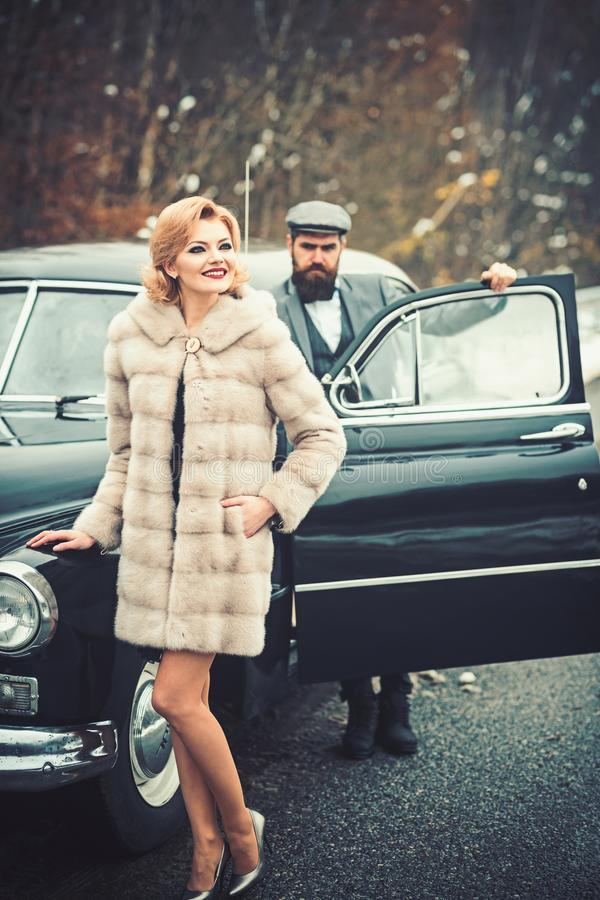 Bearded man and sexy woman in fur coat. Escort of girl by security. Retro collection car and auto repair by mechanic. Bearded men and sexy women in fur coat stock photography