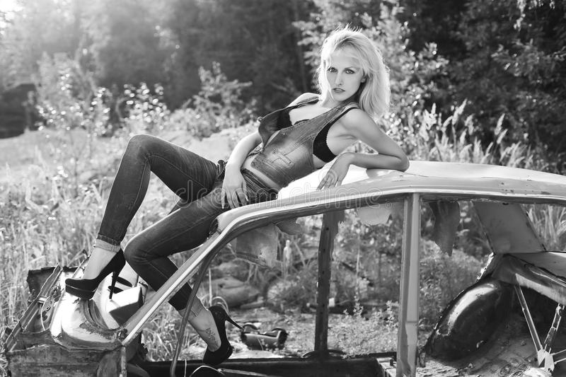 Beautiful, elegant, girl blonde in jeans in black shoes sits on the old car in the forest stock images