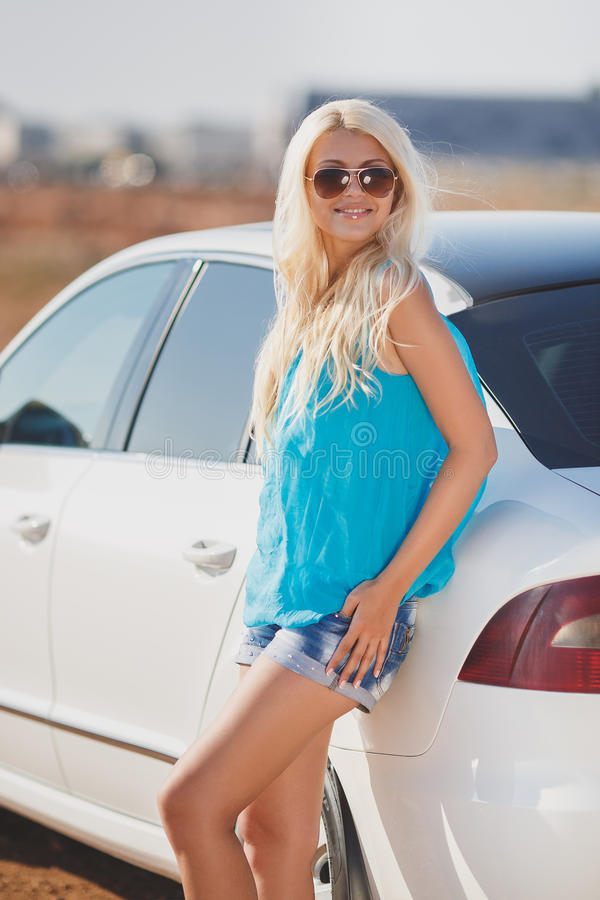 Beautiful young woman near a car outdoor. Beautiful young woman near car outdoor. Rich hot blond slim girl with long healthy hair posing with luxury expensive royalty free stock photo