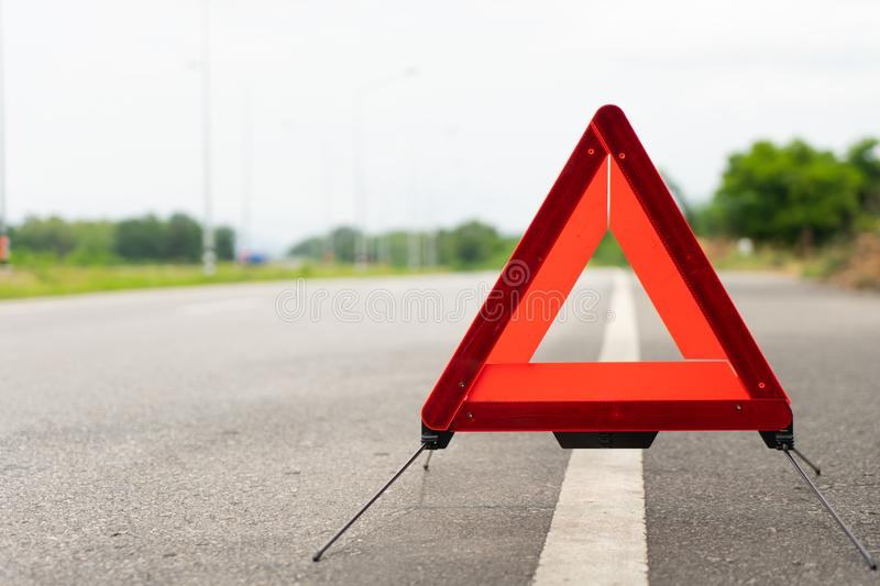 Breakdown triangle stands alongside the road. Broken car sign on a road concept.  stock photography