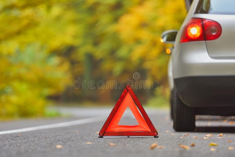 Broken car concept, breakdown triangle stop sign on road. Broken car concept, breakdown triangle stop sign on forest road royalty free stock images