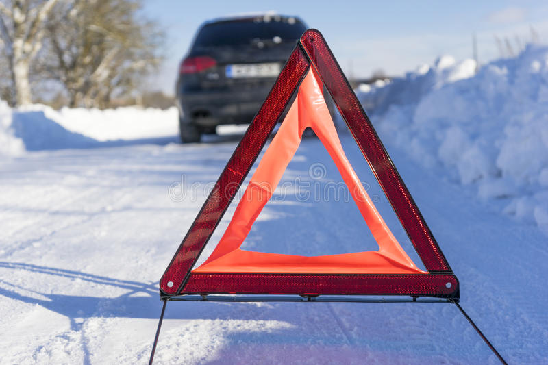 Broken car on winter road with warning sign. Image of Broken car on winter road with warning sign stock images