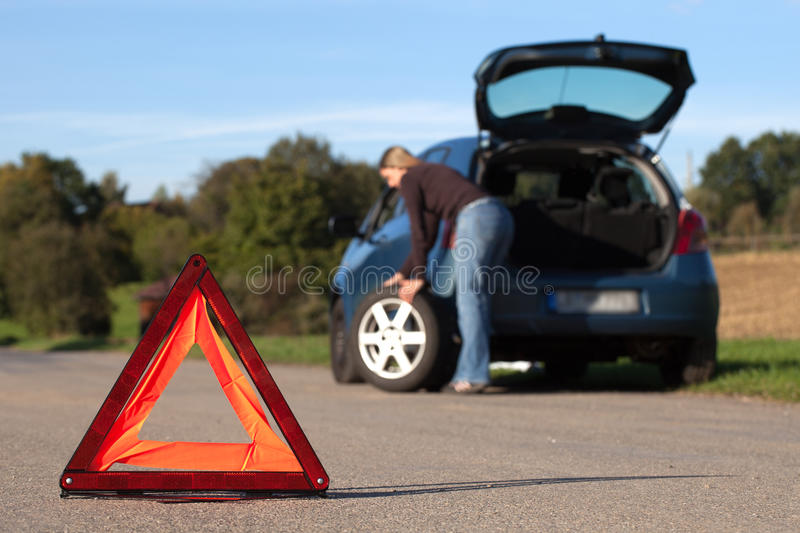 Broken down car with red warning triangle. Broken down car on a road with red warning triangle stock photo
