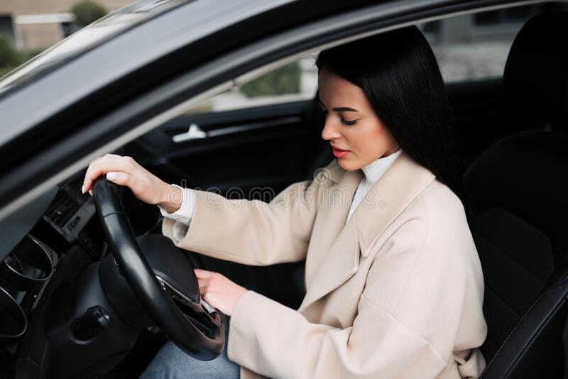 Businesswoman driving the luxury car. Girl posing in her car royalty free stock photos