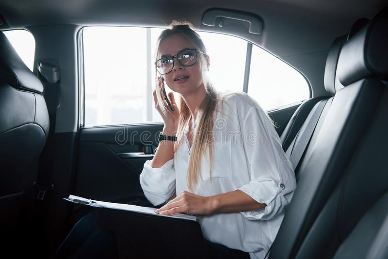Busy girl. Smart businesswoman sits at backseat of the luxury car with black interior.  royalty free stock photo