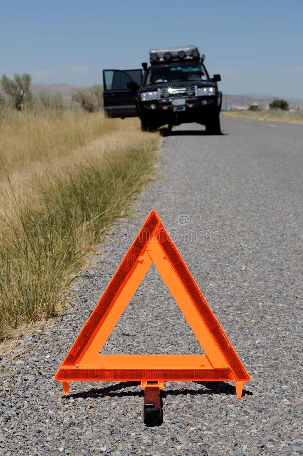 Car broken down on road with warning triangle. Large 4x4 car or truck broken down with mechanical issues on road with orange emergency warning triangle or sign royalty free stock image