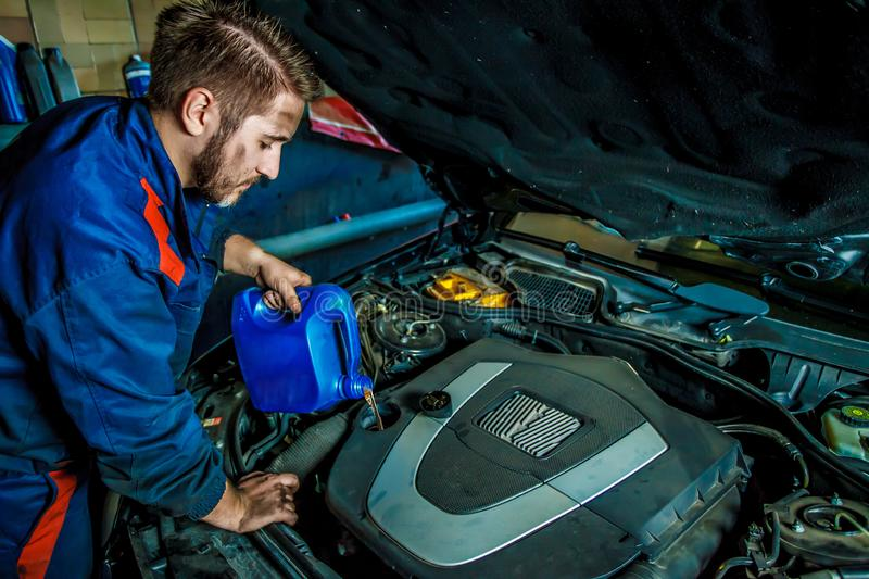 Car mechanic replacing and pouring oil into engine at maintenance repair service station. royalty free stock photography