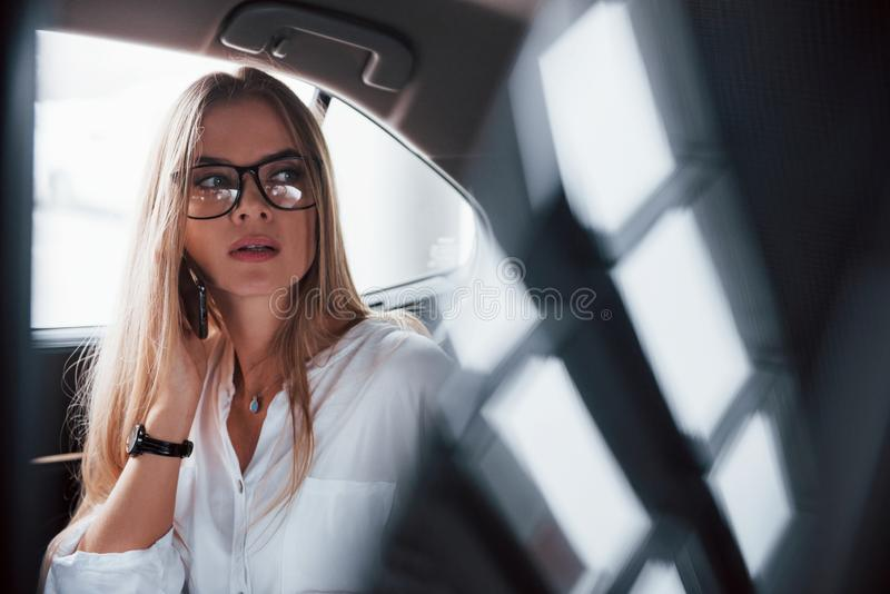 Charming serious girl. Smart businesswoman sits at backseat of the luxury car with black interior.  stock photos