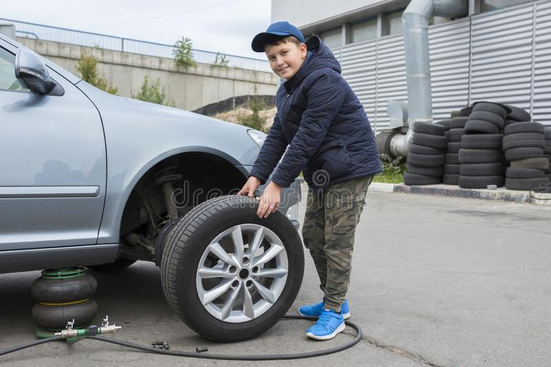 Childrens auto mechanic changes the wheel on a car. Replacing wheels on a car stock photography
