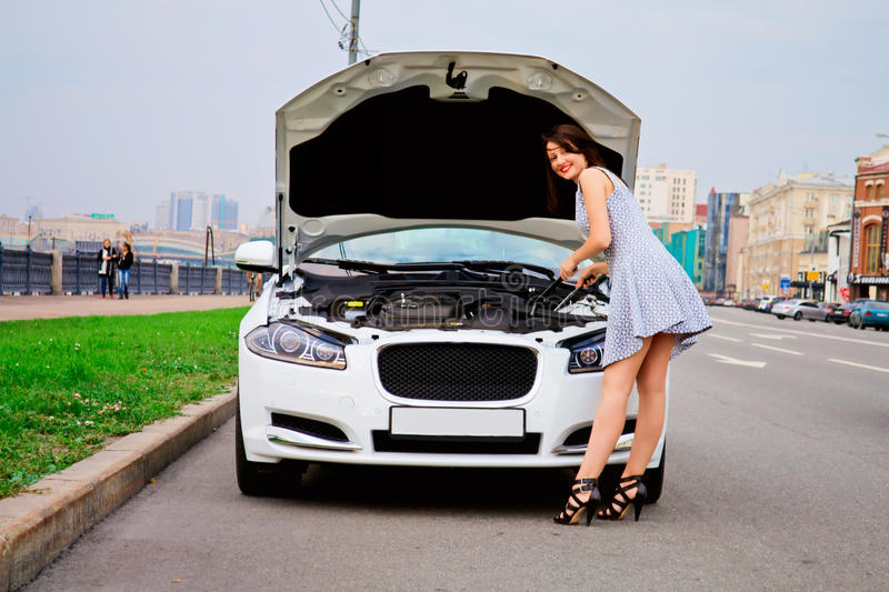 Cute brunette and luxury car. Cute brunette with red lips on high heels is posing with luxury white car (Jaguar XF) outdoor. Repairing car