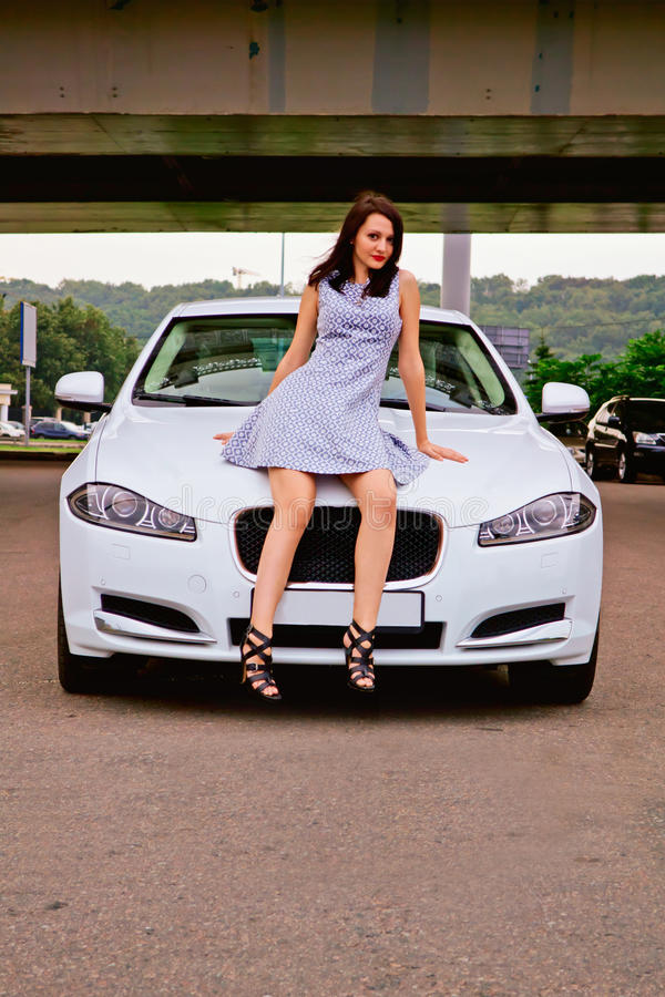 Cute brunette and luxury car. Cute brunette with red lips on high heels is posing with luxury white car (Jaguar XF) outdoor. Sitting on the car royalty free stock photos