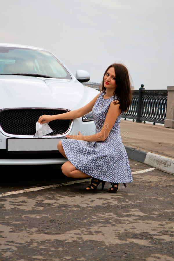 Cute brunette and luxury car. Cute brunette with red lips on high heels is posing with luxury white car outdoor. Cleaning brand logo of the car stock images