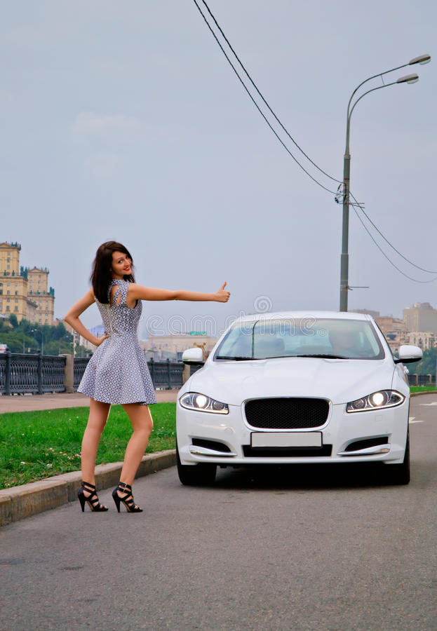 Cute brunette and luxury car. Cute brunette with red lips on high heels is stopping luxury white car (Jaguar XF) outdoor. Hitch-hiking stock image