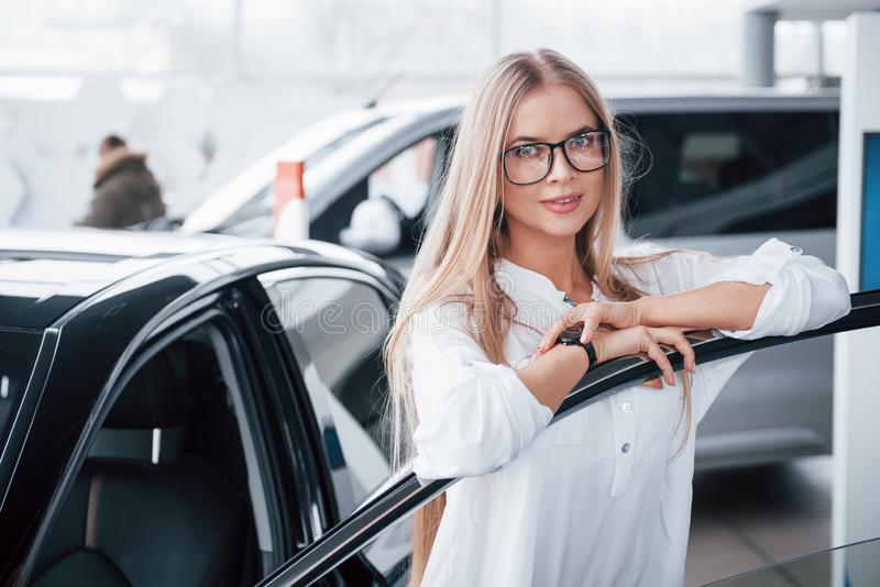 Cute girl in eyewear stands near the car in auto saloon. Probably her next purchase.  royalty free stock photos