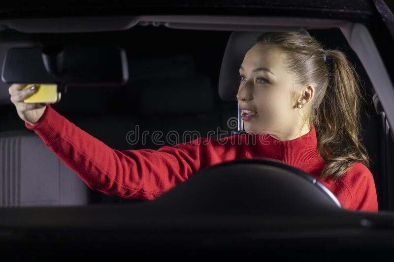 Cute long hair brunette girl in red sweater driving car at night makes selfies. Shares photos in social networks, uses royalty free stock images