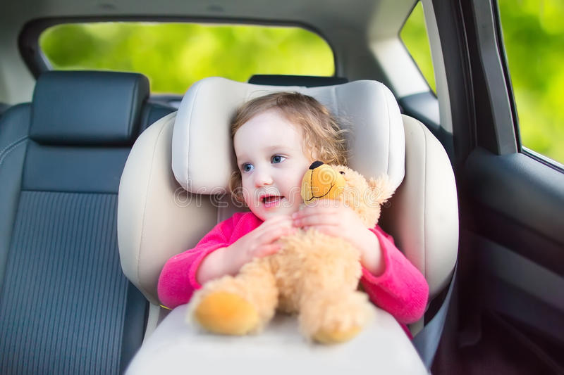 Cute toddler girl in a car seat during vacation trip. Cute curly laughing and talking toddler girl playing with a toy bear enjoying a family vacation car ride in royalty free stock photo