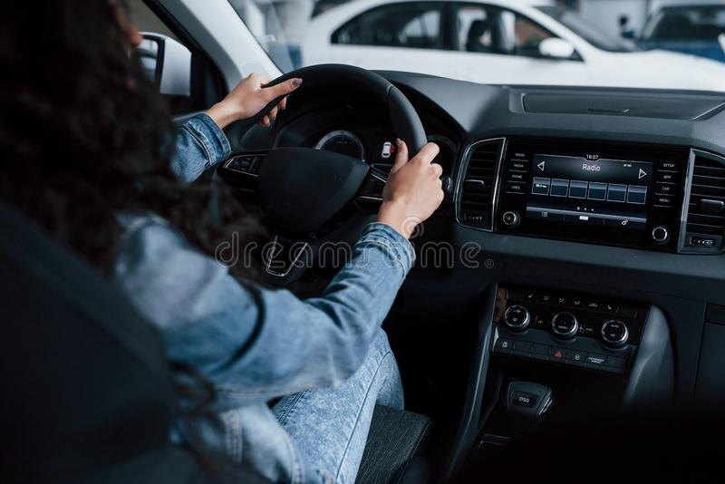 Different buttons and knobs. Cute girl with black hair trying her brand new expensive car in the automobile salon.  royalty free stock images