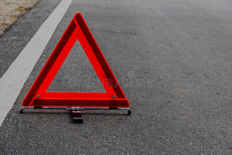 Emergency red warning triangle on the road sign with the white road line and broken car. For any design concept royalty free stock images
