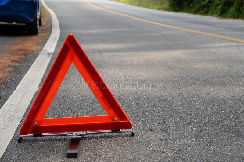 Emergency red warning triangle on the road sign with the white road line and broken car. For any design concept stock photo
