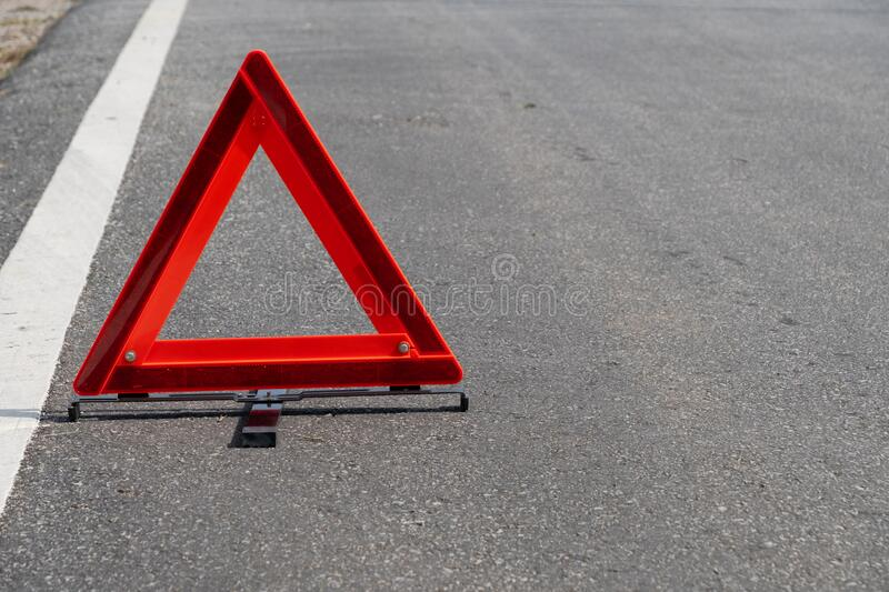 Emergency red warning triangle on the road sign with the white road line and broken car. For any design concept royalty free stock image