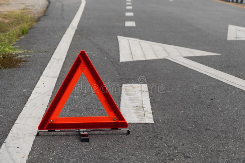 Emergency red warning triangle on the road sign with the white road line and broken car. For any design concept stock photography
