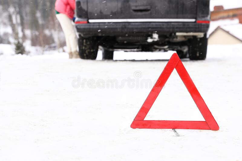 Emergency stop sign and broken car on snowy road in winter. Emergency stop sign and broken car on snowy road royalty free stock images