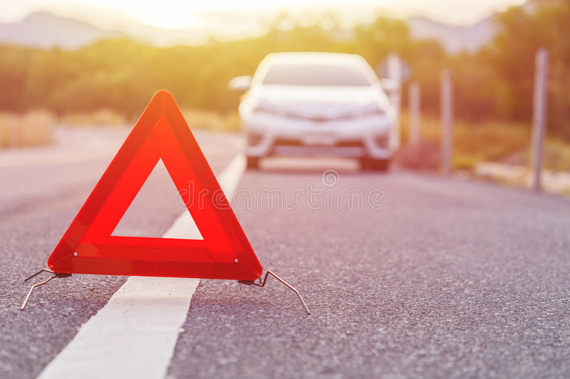 Emergency stop sign and broken silver car on the road. Red emergency stop sign and broken silver car on the road royalty free stock images