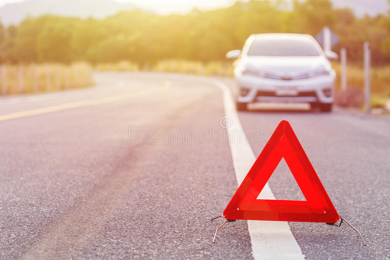 Emergency stop sign and broken silver car on the road. Red emergency stop sign and broken silver car on the road stock image