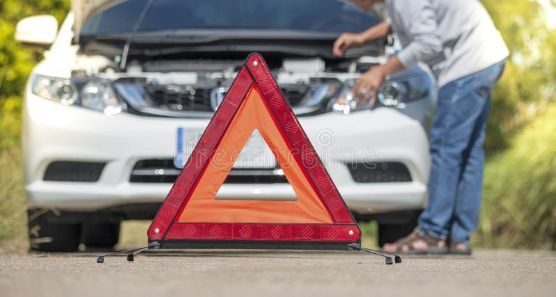 Emergency stop sign and driver near broken car on road. Car stock photography