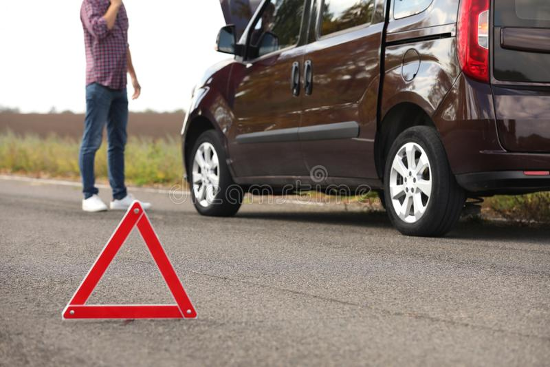Emergency stop sign and driver near broken car on road. Auto insurance stock photo