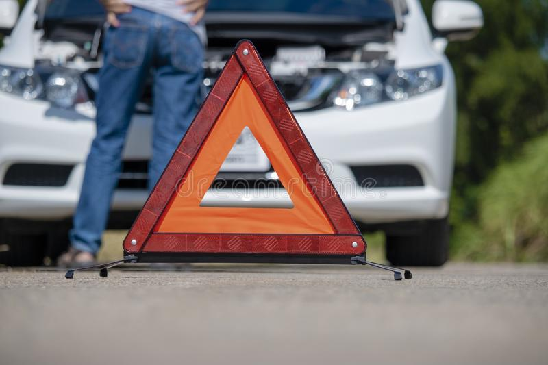 Emergency stop sign and driver near broken car on road. Boring ,warning sign ,broken car royalty free stock photo