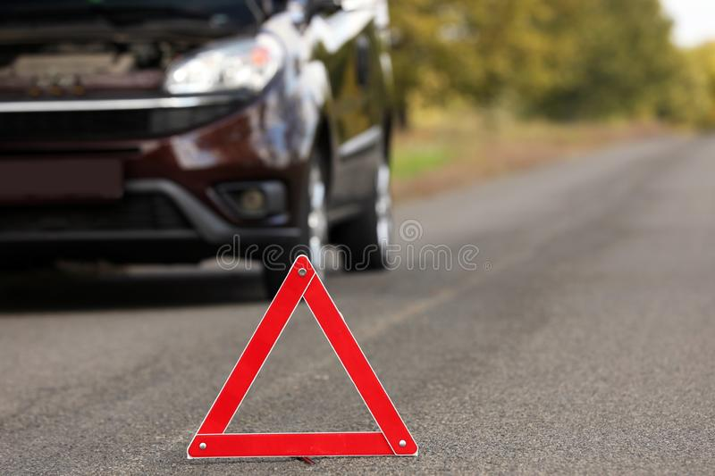 Emergency stop sign near broken car on road. Auto insurance royalty free stock photography