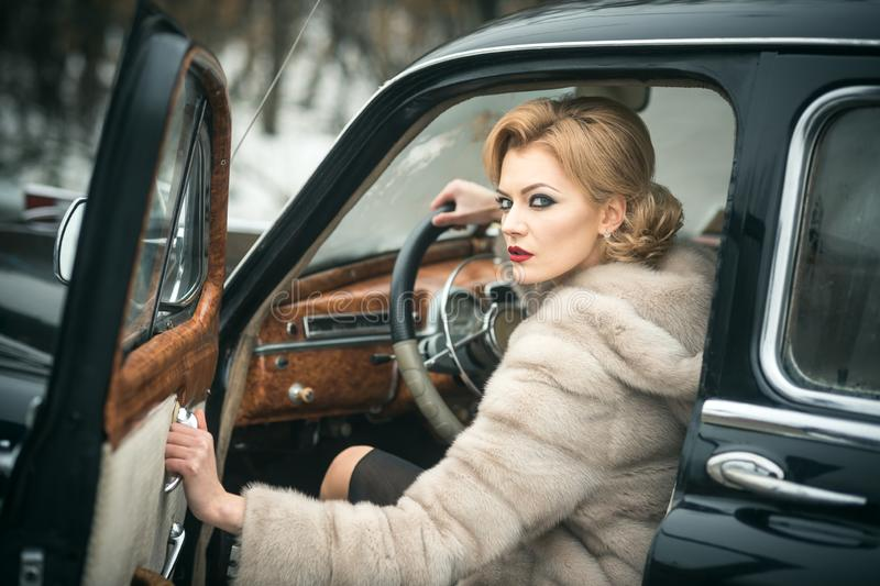 Escort and security guard for luxury woman. sexy woman in fur coat. Call girl in vintage car. Retro collection car and. Auto repair by driver. Travel and stock image