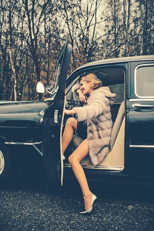 Escort and security guard for luxury woman. Travel and business trip or hitch hiking. Call girl in vintage car. sexy. Woman in fur coat. Retro collection car royalty free stock photos