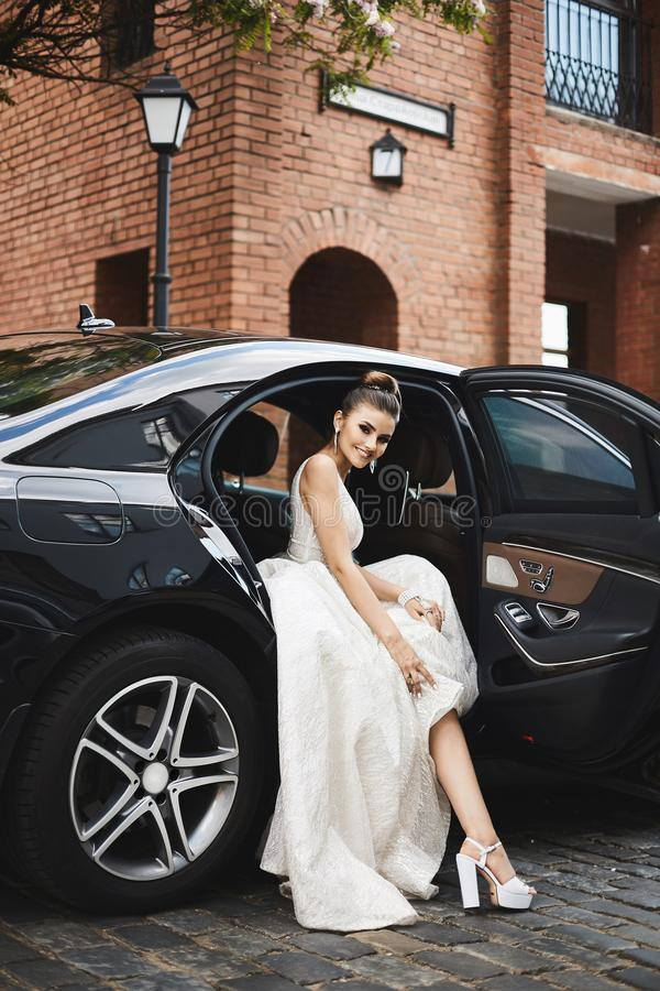 Fashionable and long legged brunette model girl with bright makeup in a trendy silver dress sits in the luxury car.  stock images
