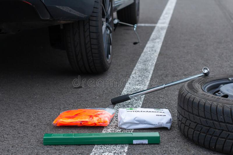 First aid, safety orange vest and green road sign on a asphalt road on the background of a broken car. Emergency tool kit for the. First help after car accident royalty free stock image
