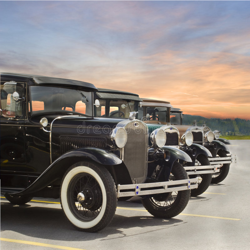 Ford Vintage Model A. Photo of Four vintage Ford Model A automobiles parked in lot with sunset in background stock photo