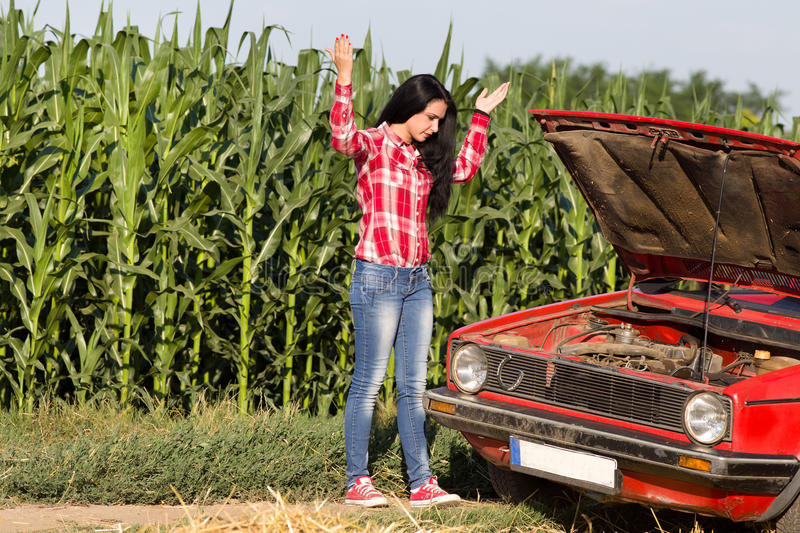 Girl with broken car. Young attractive girl standing beside broken car at rural road stock image