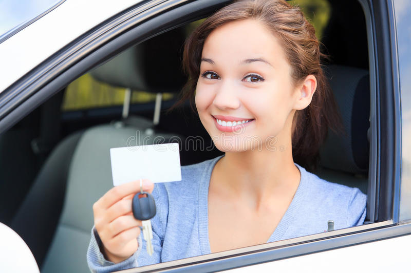 Girl in a car. Happy girl in a car showing a key and an empty white card for your message royalty free stock image
