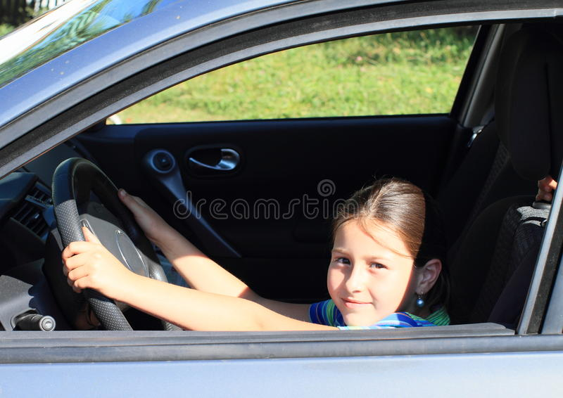 Girl driving a car. Smiling girl holding steering wheel and driving a silver car with opened window stock images