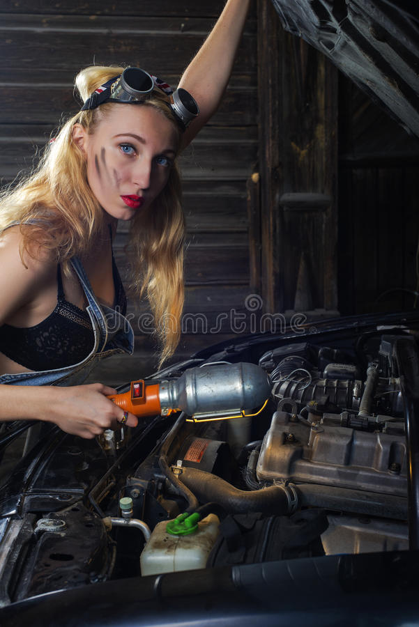 Girl is repairing car. Mechanic girl in the welder`s glasses is repairing the car in the garage royalty free stock photography