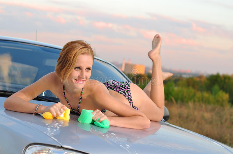 Girl Washing Car. The girl washes the car outdoor royalty free stock photography