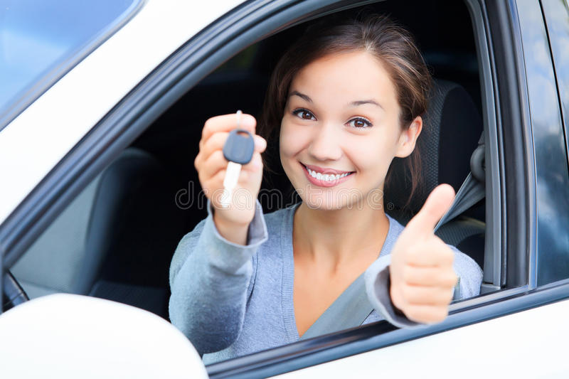 Happy girl in a car showing a key. And thumb up gesture stock images