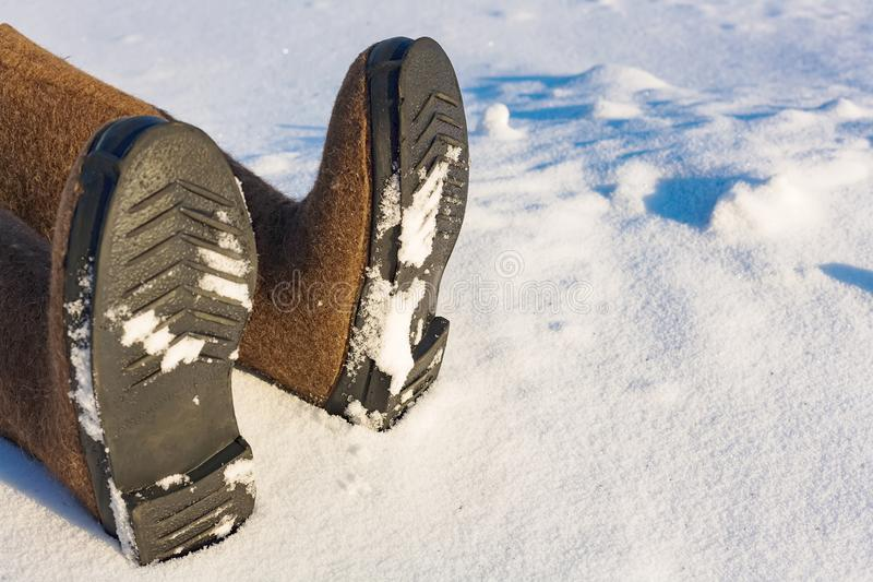 Human legs in warm felt shoes on the side of the snow. Place to copy information about frostbite or accident in the winter in the stock images